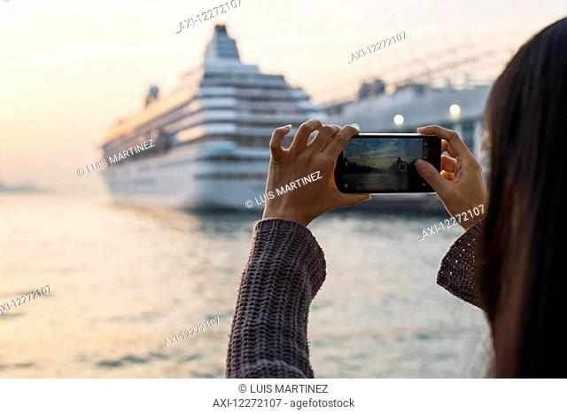 A young woman photographs a cruise ship in the harbour at sunset, Kowloon; Hong Kong, China