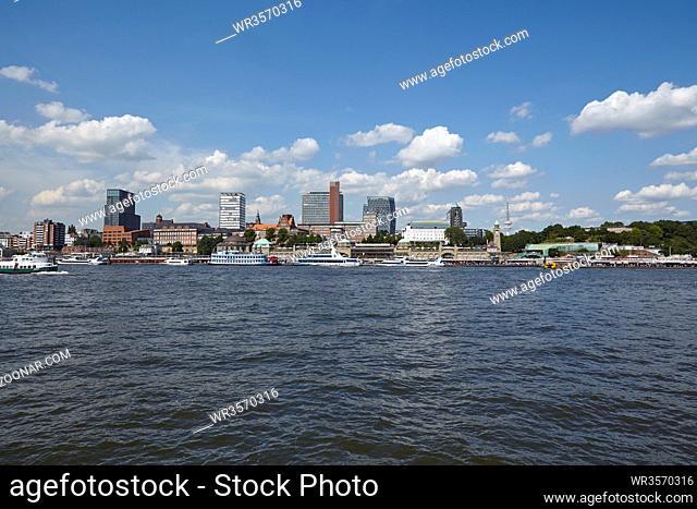 Die Skyline des Hamburger Hafens mit dem Michel und den St. Pauli Landungsbrücken bei Tageslichet mit blauen Himmel und weißen Wölkchen am 8