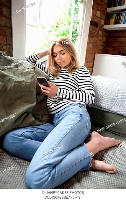 Young woman relaxing on sofa, looking at smartphone