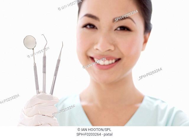 Female dentist holding dental instruments