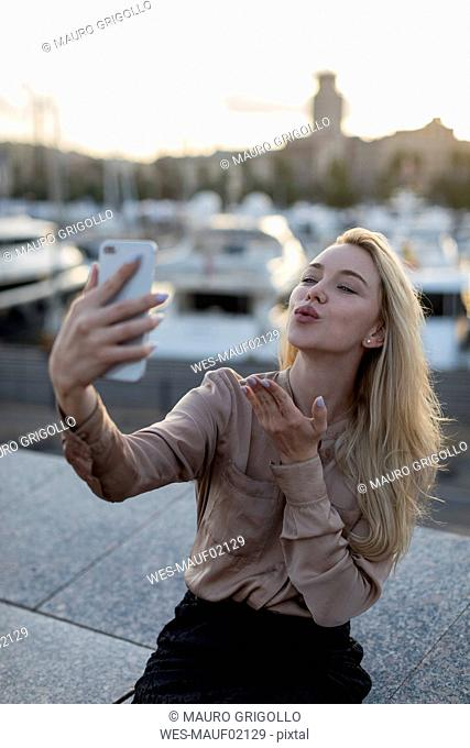 Young woman taking a selfie and blowing a kiss at the waterfront