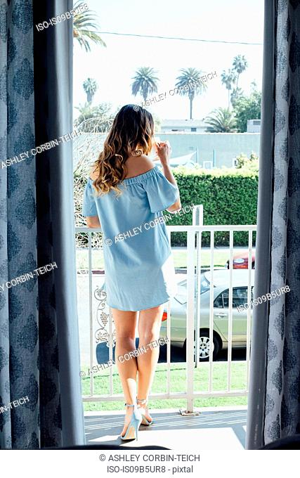 Sophisticated young woman looking out from patio drinking coffee