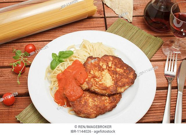 2 Milanese turkey steaks on spaghetti with tomato sugo, carafe and glass of red wine, piece of Parmesan cheese, spaghetti in glass