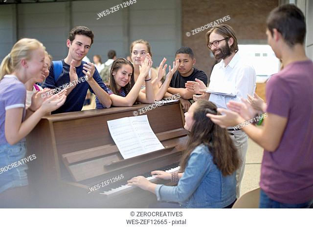 Teacher with group of students standing around piano and applauding