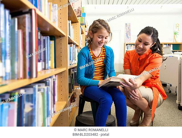 Teacher and student reading together in library