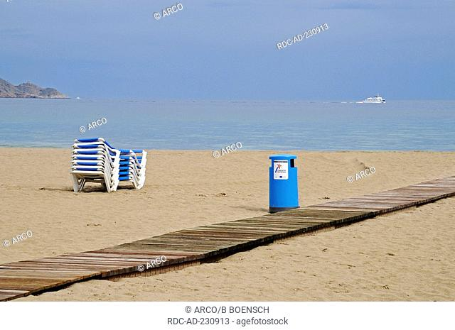 Pile of beach chairs at unpeopled beach, Playa de Poniente, Benidorm, Costa Blanca, Spain