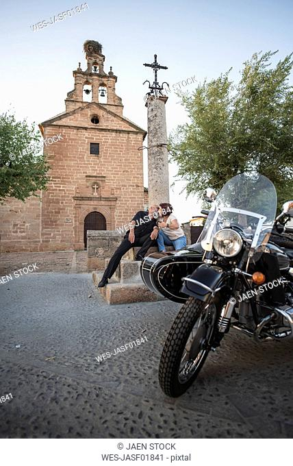 Spain, Banos de la Encina, mature couple with motorcycle with a sidecar kissing at a church
