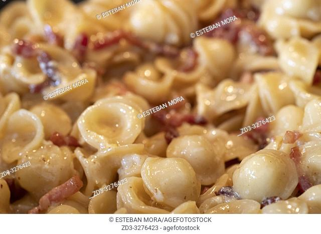Cooking Pasta Orecchiette alla Carbonara in a pan