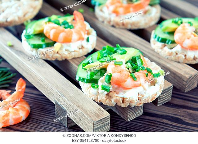 Rice cakes with sliced avocado cucumber shrimp and cream cheese. Fresh parsley and rosemary. Vegetarian, vegan concept. Shallow depth of field
