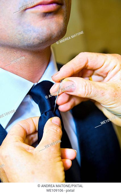 Groom putting a cravat pin on