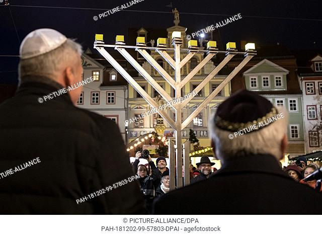 02 December 2018, Thuringia, Erfurt: The first candle shines on the Hanukkah lamp in front of the town hall at the beginning of the Jewish Hanukkah Festival of...