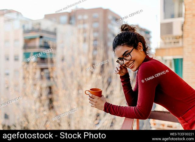 Portrait of young woman wearing red turtleneck pullover, hand on glasses, standing with a cup on a balcony