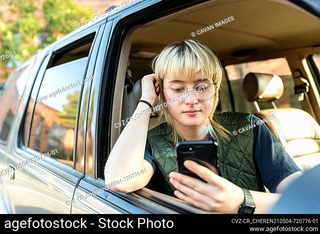 Teenager sitting in passenger seat of car looking at cell phone