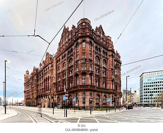 Cityscape with red brick hotel on corner site, Manchester, UK