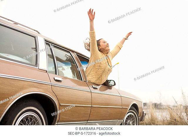 Woman (18-19) in car leaning out of window