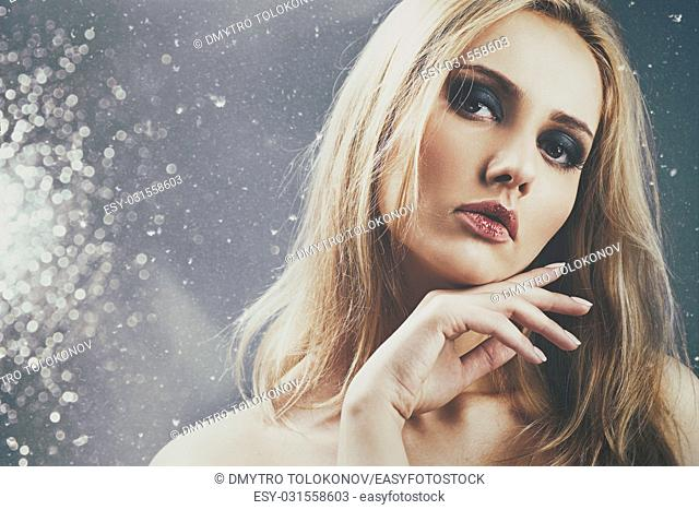 Studio female portrait. Beauty adult woman posing in studio with abstract bokeh as background