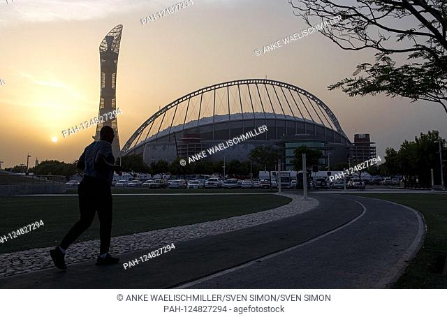 A jogger in front of the Khalifa International Stadium in the Aspire Zone, Doha Sports City, evening mood, on 26.09.2019 World Athletics Championships 2019 in...