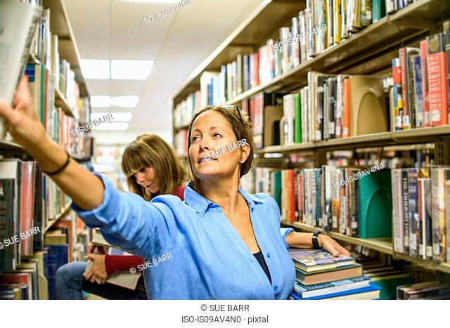 Mature woman searching for books in library