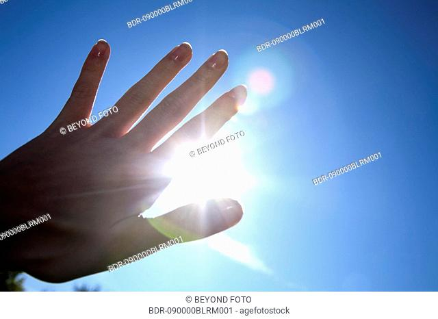 close-up of hand in front of blue sky with burning sun