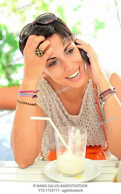 Attractive young woman with summer style drinks a juice and speaks on the mobile phone