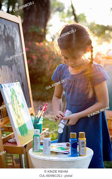 Girl squeezing paint onto palette in garden