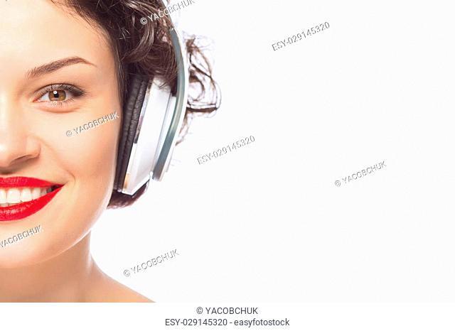 Posing with headphones. Young appealing woman wearing headphones