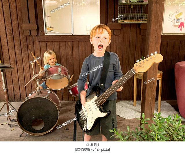 Children playing guitar and drums in band