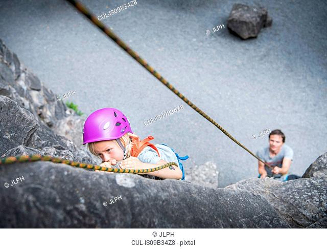 Boy wearing climbing helmet rock climbing