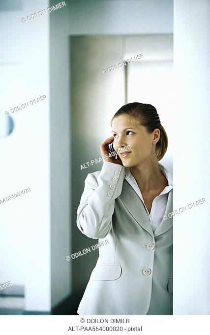 Businesswoman using cell phone, glancing away