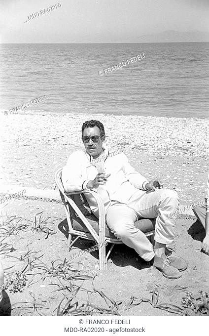Mexican-born American actor Anthony Quinn (Antonio Rodolfo Quinn Oaxaca) relaxing by the sea during a break on the set of the film The Guns of Navarone