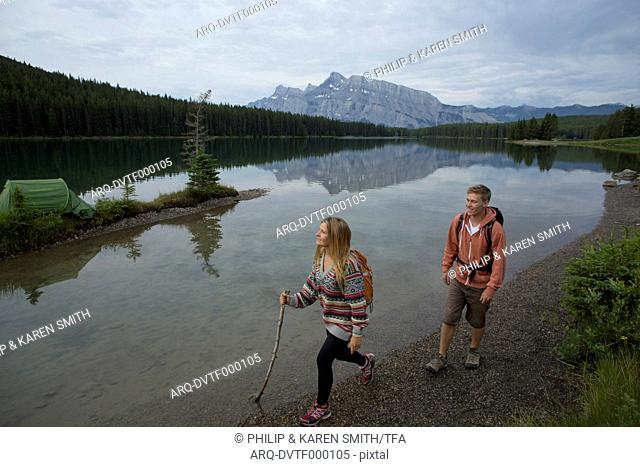 Young couple hikes along mountain lake