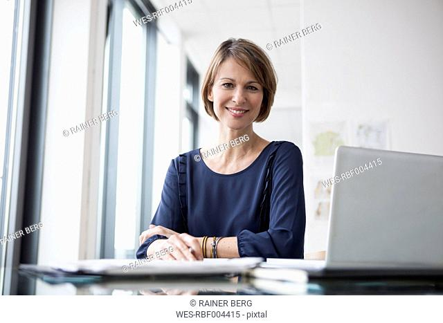 Portrait of smiling businesswoman at office desk
