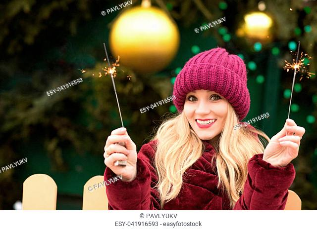 Funny young woman dressed in trendy apparel, holding sparkling bengal lights at the new Year's spruce in Kyiv