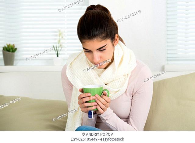 Sad young woman holding tee mug while sitting on sofa at home