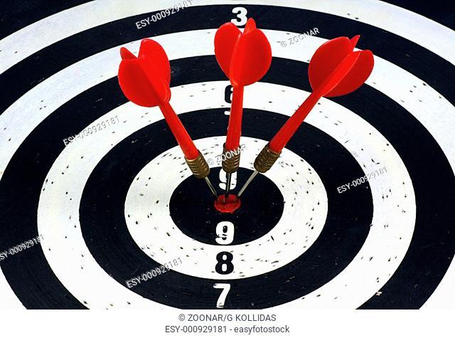 Three red darts hitting a target board