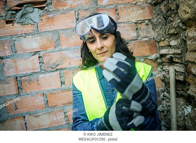 Woman on construction site putting on protective gloves