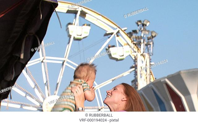 Woman with baby laughing at amusement park