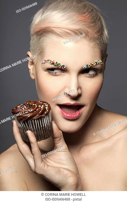 Young woman holding cupcake