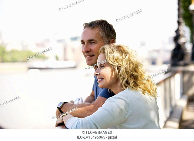 A middle-aged couple standing next to the river Thames, admiring the view