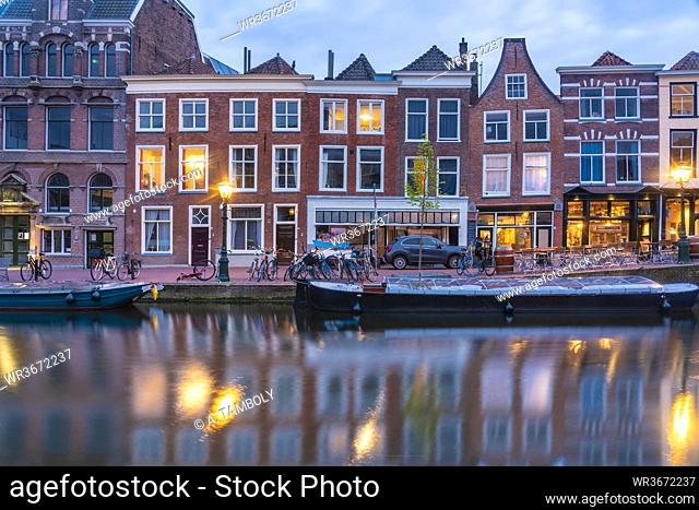 Netherlands, South Holland, Leiden, Row of historical townhouses along Rhine canal at dusk