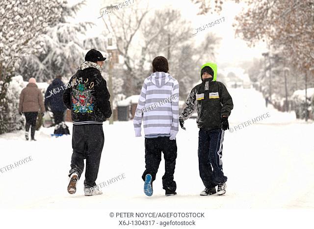 three teenagers walking down snow covered suburban street