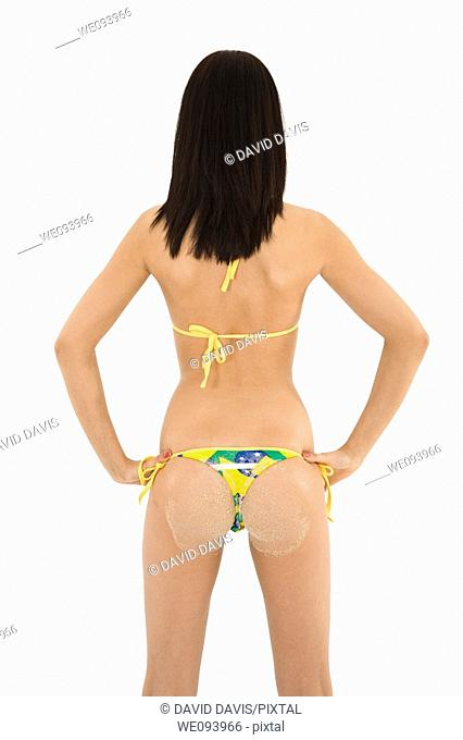 Beautiful and sexy caucasian woman in her early 20s posing in a Brazilian bikini She is standing with her back to the camera and has sand on her butt  She is...