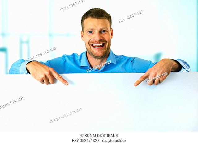 young smiling man pointing on white blank board with copy space