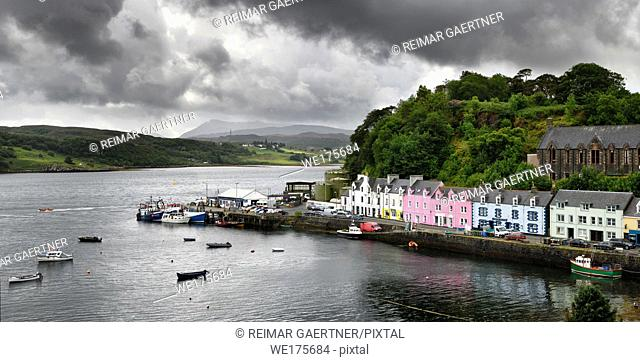 Colorful houses on Quay street of Portree Harbour on the Isle of Skye Inner Hebrides Scottish Highlands Scotland with boats and dark clouds