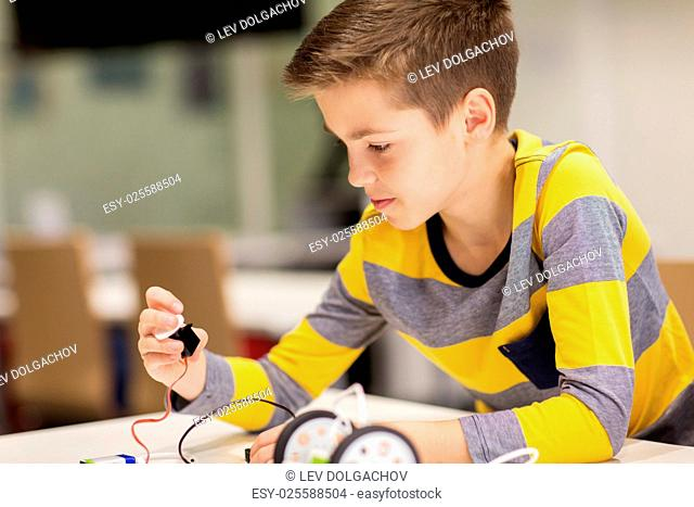education, children, technology, science and people concept - close up of boy building robot at robotics school lesson
