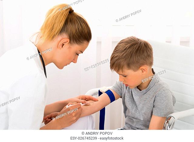 Young Female Doctor Taking Blood Sample Of Child Patient In Clinic