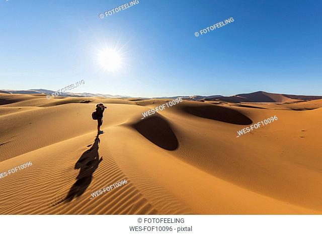 Africa, Namibia, Namib desert, Naukluft National Park, female photograper on sand dune against the sun