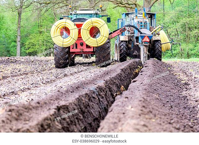 Two agriculture tractors putting pipes in ground for water drainage