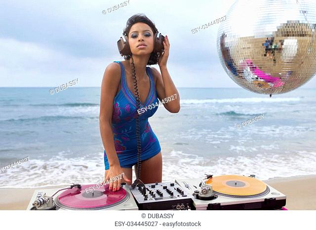 beautiful sexy latin bomb-shell djing at a beach in the early morning. useful for style fashion and music events