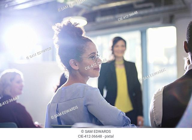 Businesswoman turning, listening in conference audience